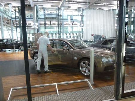 The white uniforms worn by a worker inspecting the Bentley